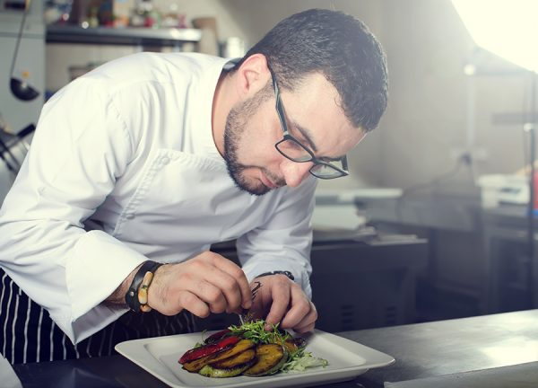 Chef wearing glasses plating a gourmet-style entree featuring fresh grilled vegetables in a professional kitchen setting.