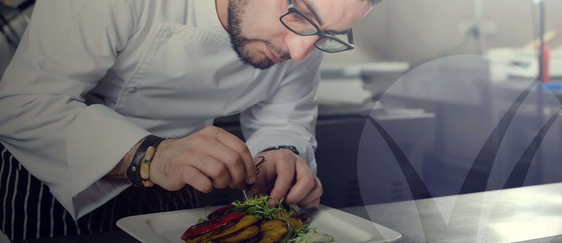 Chef wearing glasses plating a gourmet-style entree featuring fresh grilled vegetables in a professional kitchen setting. Better Homes and Gardens Real Estate