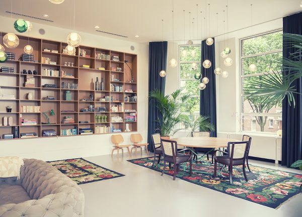 Home library featuring large open windows with window seat, table, plush couches and a large bookcase for displaying books and trinkets.