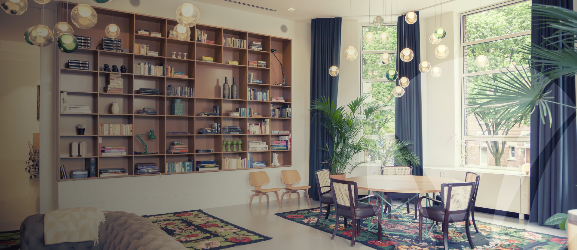 Home library featuring large open windows with window seat, table, plush couches and a large bookcase for displaying books and trinkets. Better Homes and Gardens Real Estate