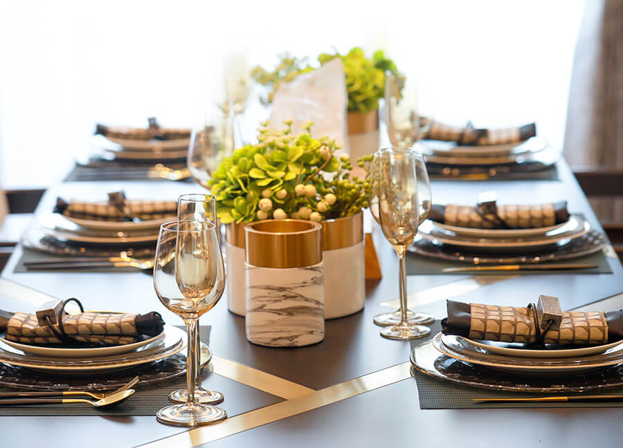 Formal set dining room table set with low succulent centerpieces and wine glasses.