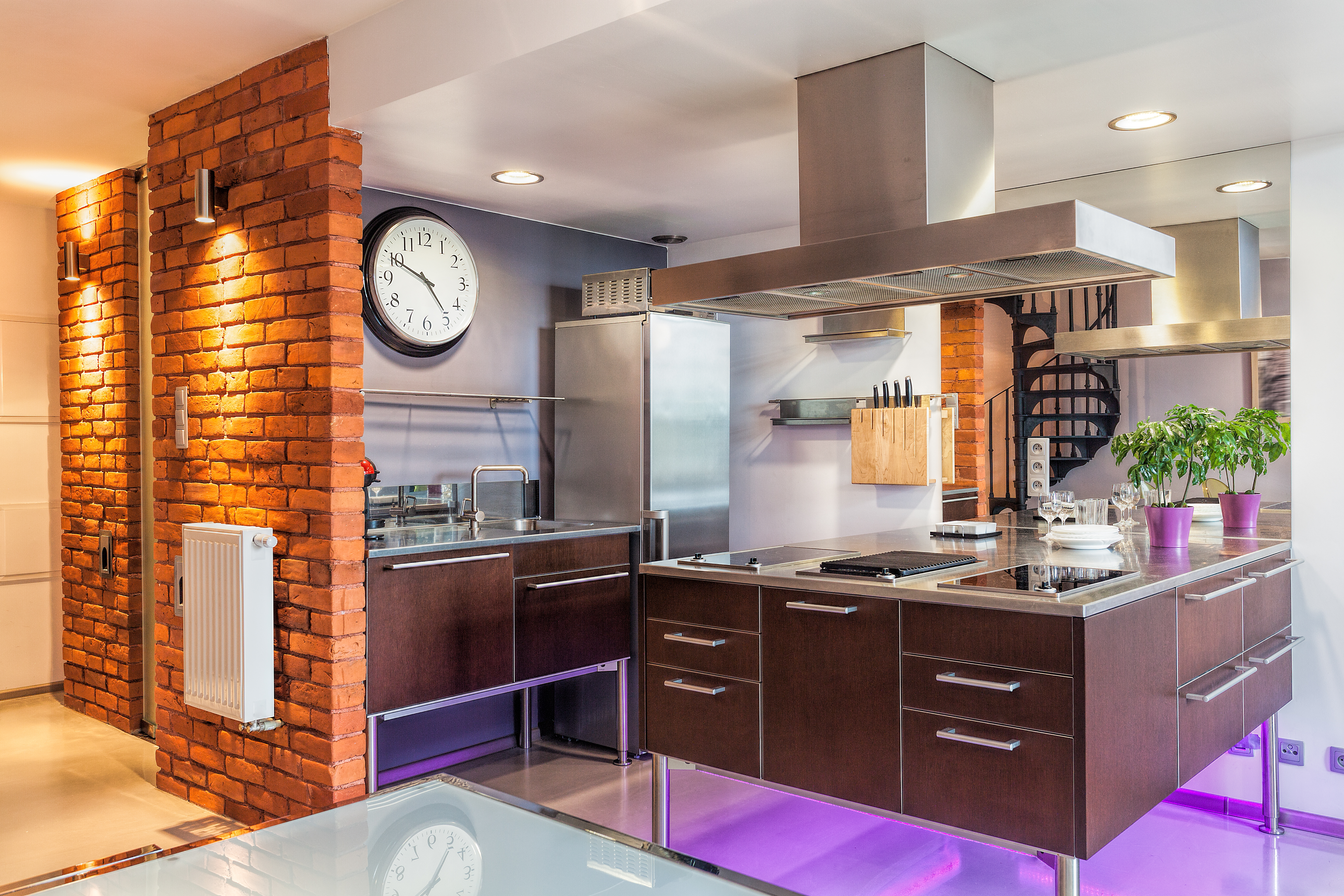 Modern kitchen featuring exposed brick and heavy use of stainless steel appliances and fixtures.