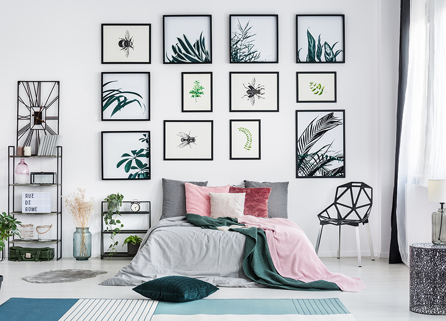 Bright sunny bedroom featuring a variety of modern-style wall art