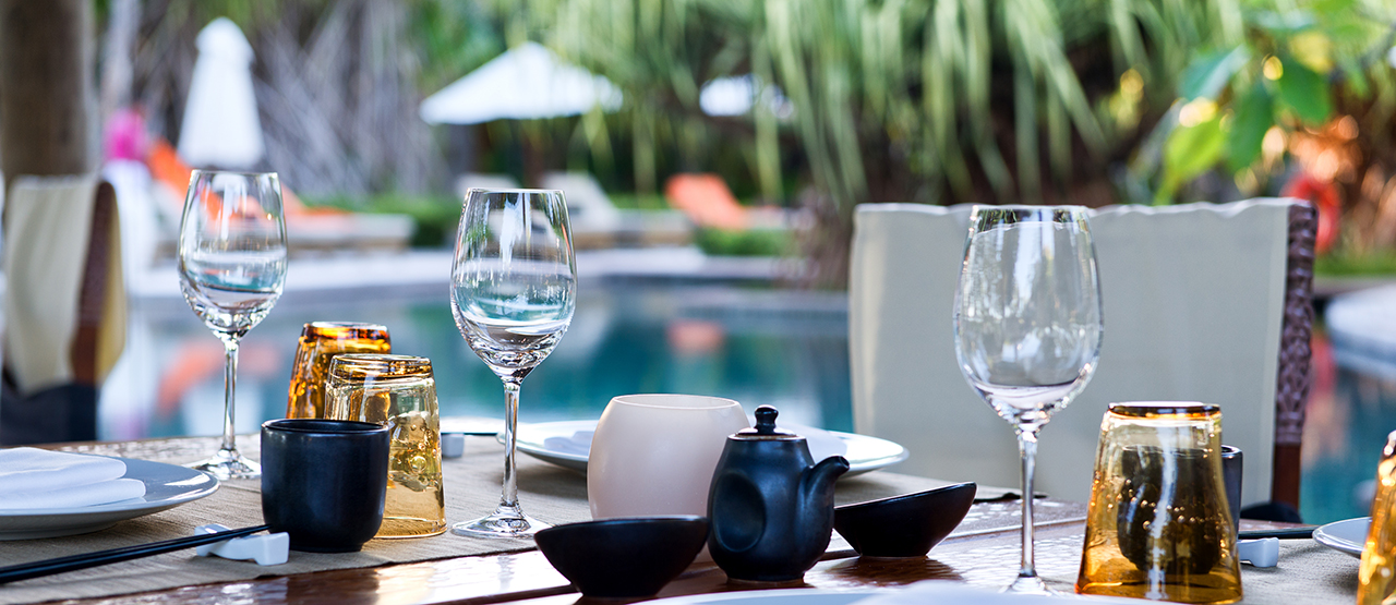 Outdoor dining table near a pool set with china and glassware
