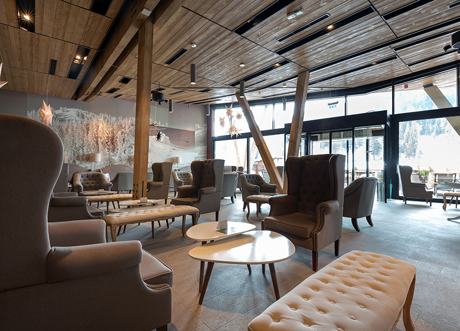 Lobby of boutique hotel featuring chic armchairs and lounges.