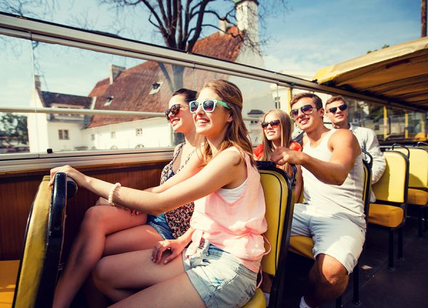 Group of young adults wearing summer outfits and sunglasses on an open-air bus taking a tour of the countryside