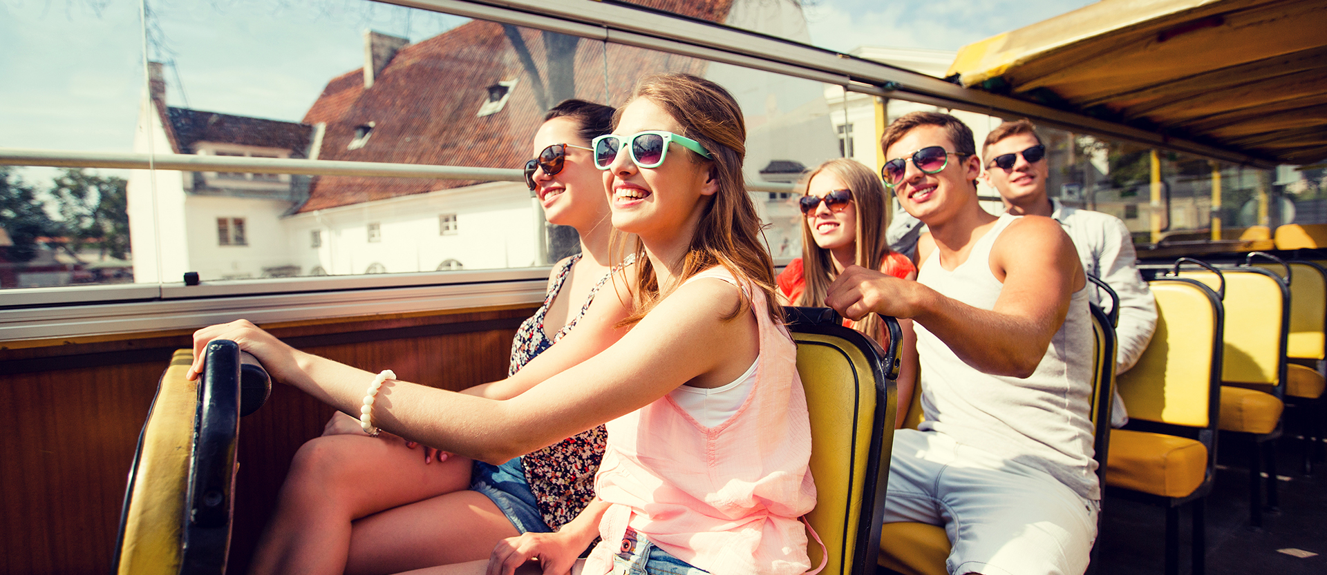 Group of young friends all wearing sunglasses on an open air tour bus in the European countryside.