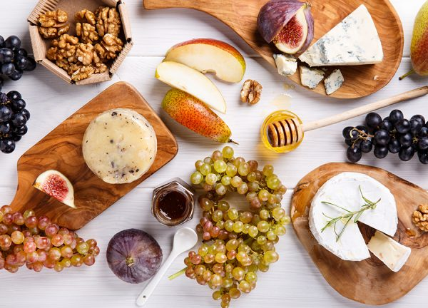 Cheese board with a variety of cheeses, fruits, nuts, and honey.
