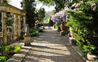 Elegant outdoor garden with stonework, a variety of florals and greenery, statues, and a marble pergola