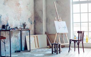 Bright room with large window displaying an artist's canvas and art supplies strewn about the table and floor.