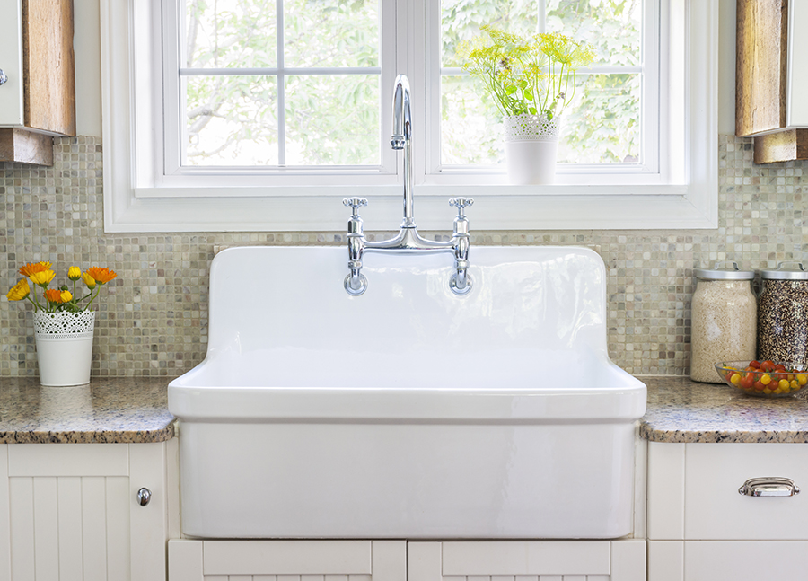 Farmhouse sink flanked by granite counter tops with a mosaic tile backsplash beneath a bright open window