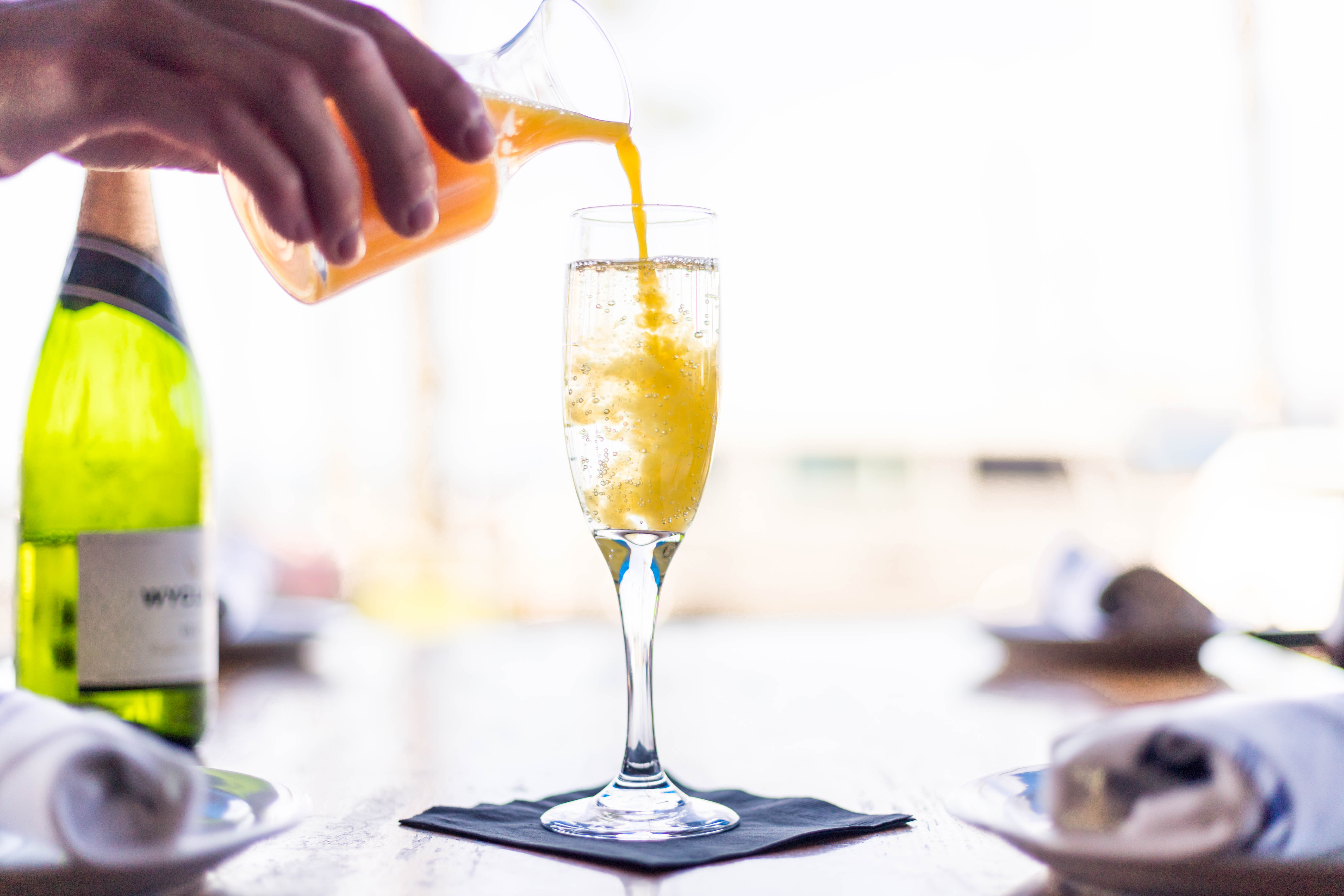 orange juice being poured in champagne glass