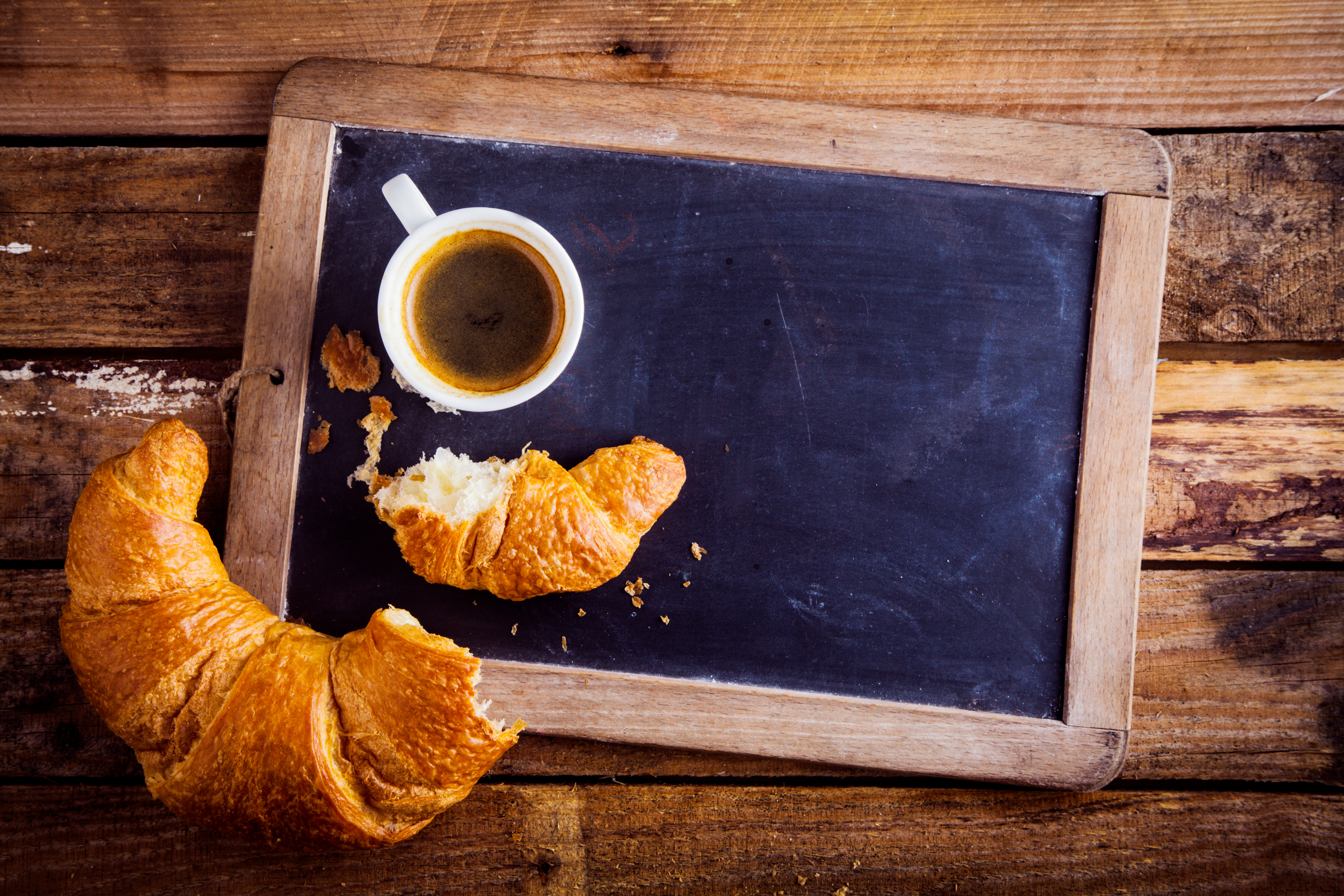 chalk board menu on table with coffee and croissant